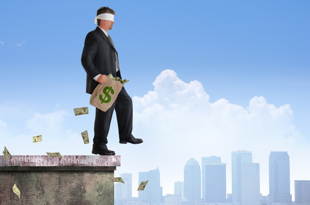 Blindfolded business man with bag of money is about to walk off the edge of a building representing financial risk, management, planning, investments, savings and retirement, and many other financial concepts.